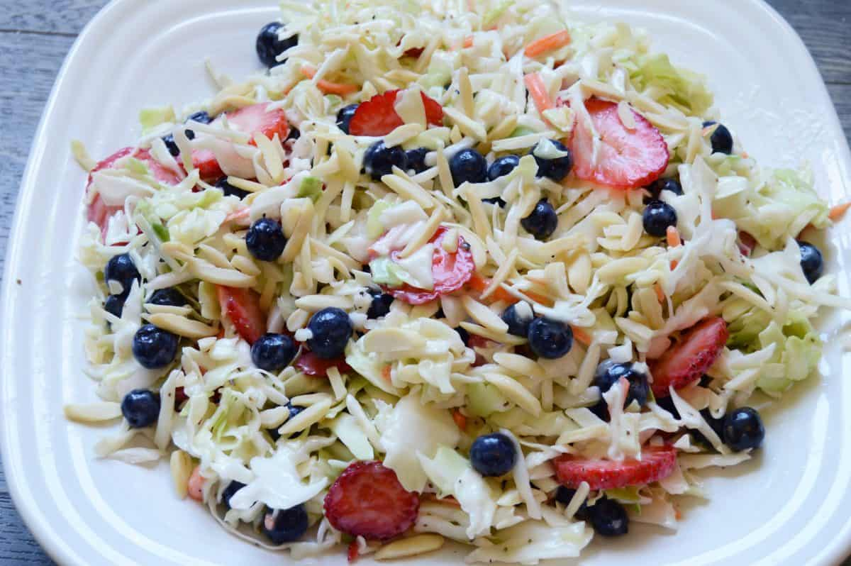 All American coleslaw made with cabbage, blueberries, strawberries and slivered almonds on a white plate
