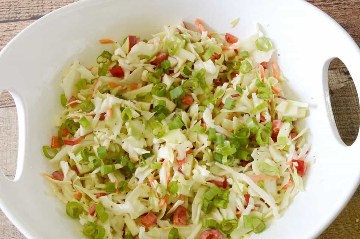 Apple slaw in a white bowl and wood background