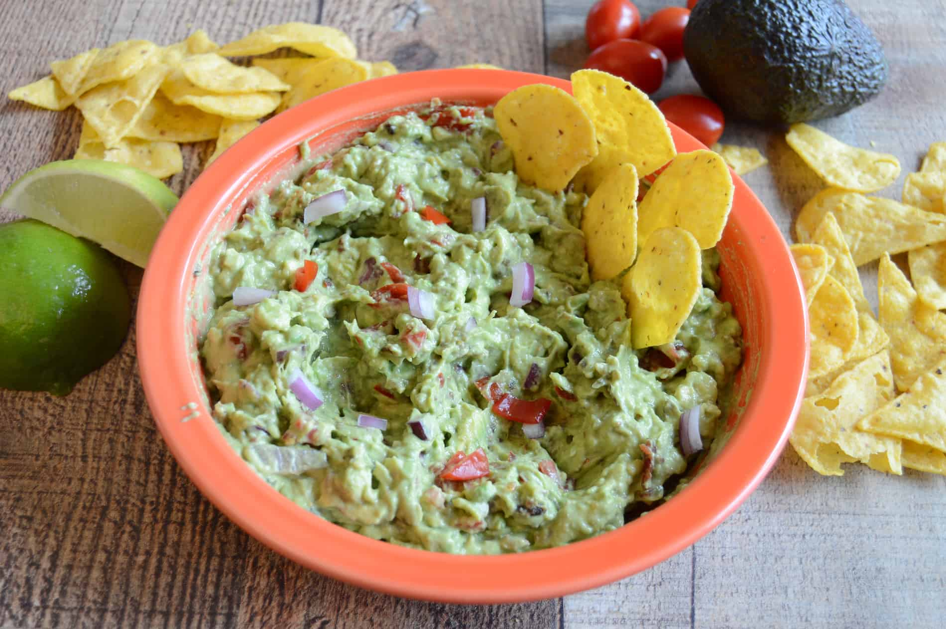 Guacamole Dip made with bacon, tomatoes and onion in a red bowl and wooden background